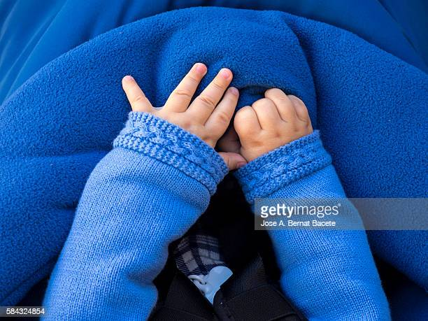 Hands of a European newborn child warm with a sweater