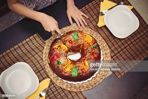 hands of a girl cutting a christmas fruitcake. - fruit cake stock pictures, royalty-free photos & images