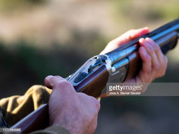 hands of a hunter loading a hunting shotgun. - hunting stock pictures, royalty-free photos & images