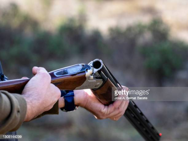 hands of a hunter with an open shotgun ejecting the cartridge during a hunting day. - rifle fotografías e imágenes de stock