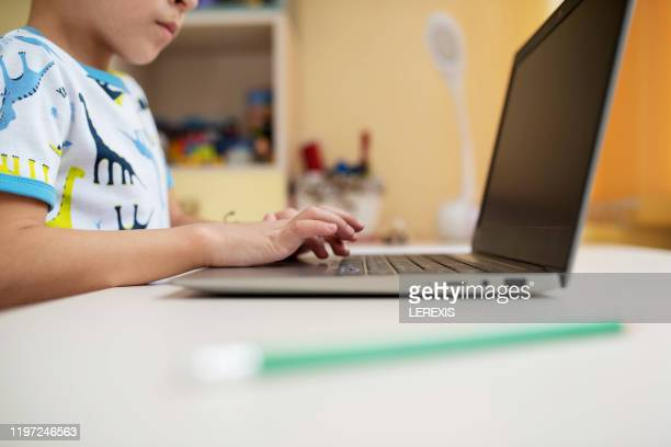 hands of a little boy on a laptop keyboard - e learning stock pictures, royalty-free photos & images