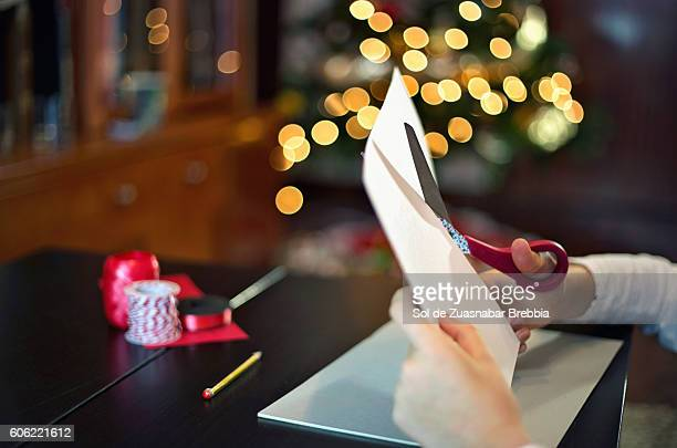 Hands of a little girl cutting a piece of paper in Christmas time.