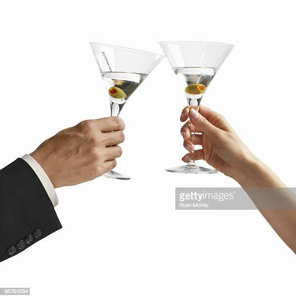 hands of a man and woman toasting - martini glass stock pictures, royalty-free photos & images