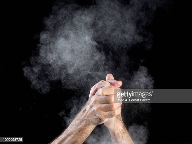 Hands of a man applauding with a cloud of powder on a black background.