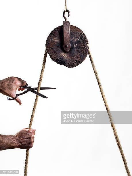 Hands of a man cutting with a few scissors a rope that happens for a pulley of ancient wood