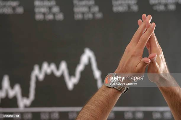 Hands of a man in front of a stock price panel