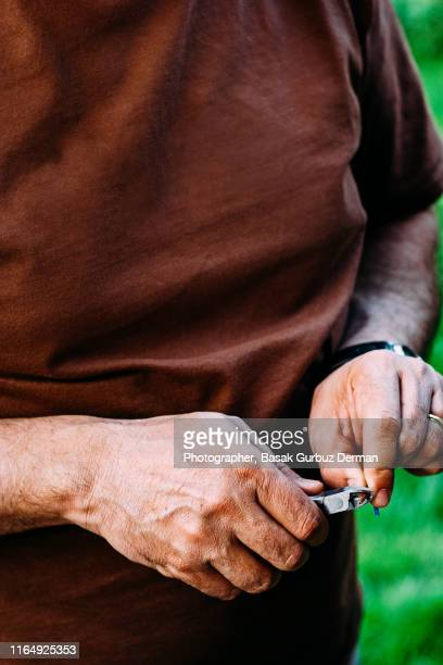 hands of a man repairing cables, cutting the red cable with a plier - basak gurbuz derman stockfoto's en -beelden