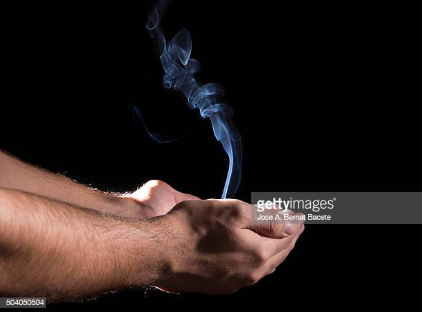 Hands of a man that take in his interior a column of smoke