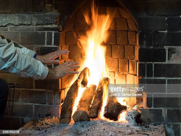 hands of a man warming up to the fire of fuelwood - warming up stock pictures, royalty-free photos & images