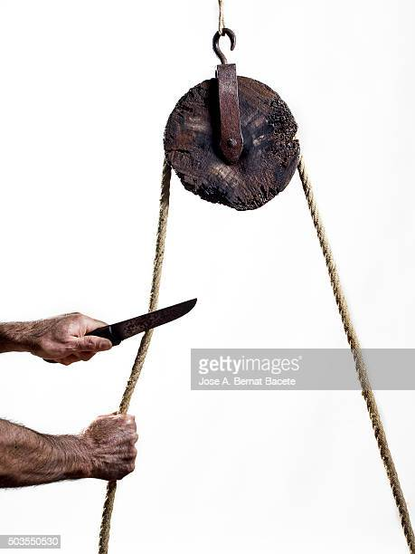 Hands of a man with a knife cutting a rope that happens for a pulley