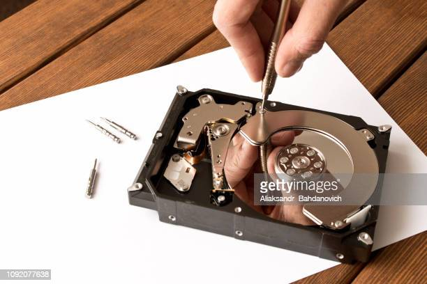 hands man with screwdriver disassembling hard