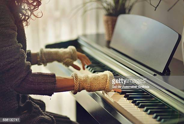 Hands of a musician playing the piano with mittens
