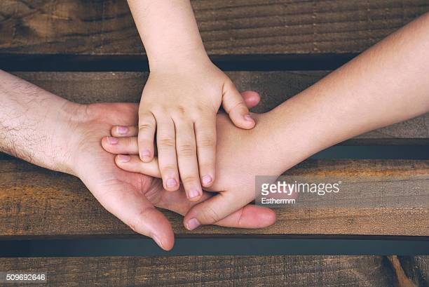 hands of a parent with their children on a wooden table