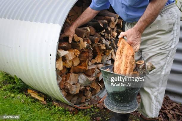 Hands of a senior man collecting  firewood