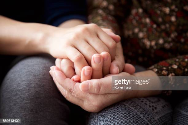 hands of a senior woman and her daughter holding each other's hands together - aanhankelijk stockfoto's en -beelden