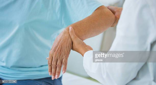 hands of a senior woman at doctor's office. - rheumatoid arthritis stock pictures, royalty-free photos & images