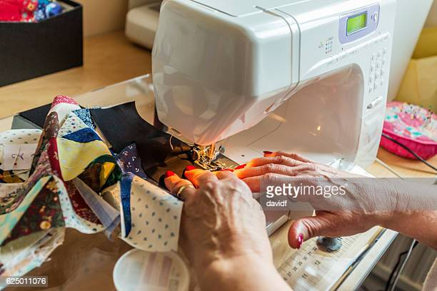 hands of a senior woman sewing quilts as a hobby - sewing machine stock pictures, royalty-free photos & images