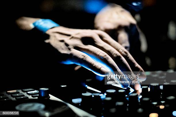 Hands of a sound engineer adjusting regulators of a professional mixer unit