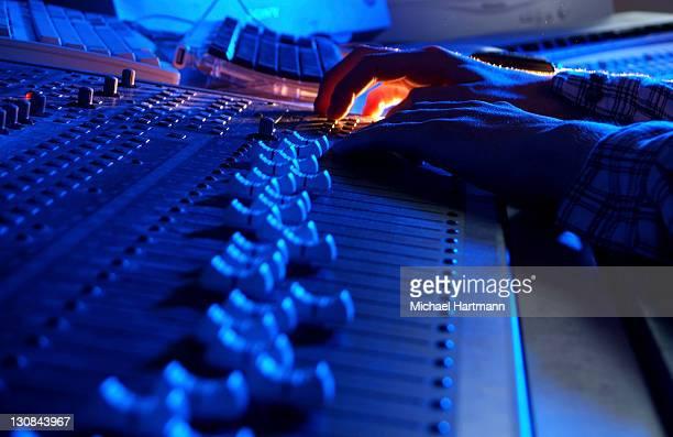 Hands of a sound engineer adjusting the regulators of a professional mixer unit