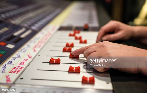 hands of a sound engineer on audio mixing console at recording studio - gol di pareggio foto e immagini stock