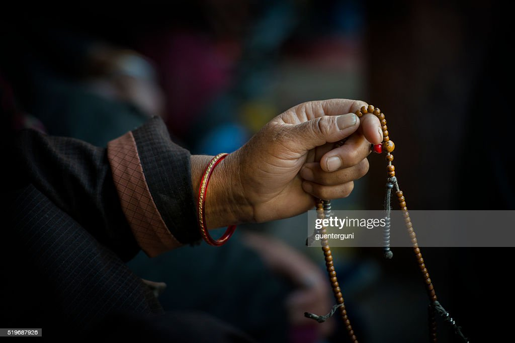 Hands of a Tibetan Buddhist with his prayer beads : Stock Photo