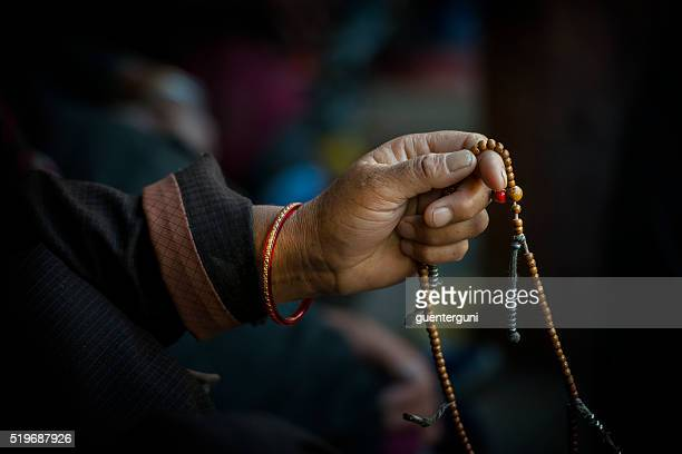 Hands of a Tibetan Buddhist with his prayer beads