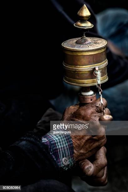 Hands of a Tibetan Buddhist with his prayer wheel