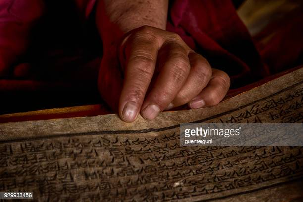 hands of a tibetan monk with an ancient prayer book - ancient stock pictures, royalty-free photos & images