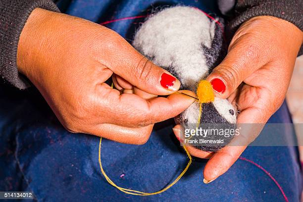 Hands of a woman are working at felt egg warmer