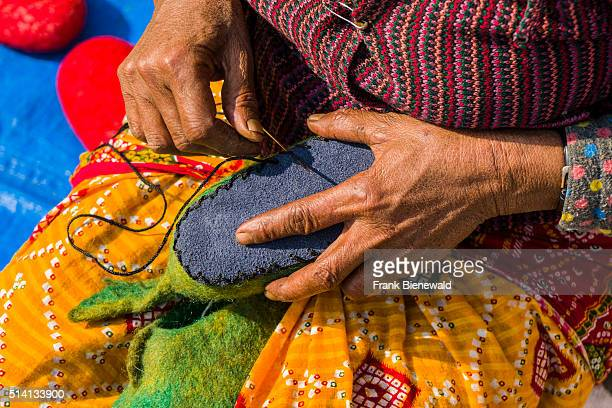Hands of a woman are working at felt shoes