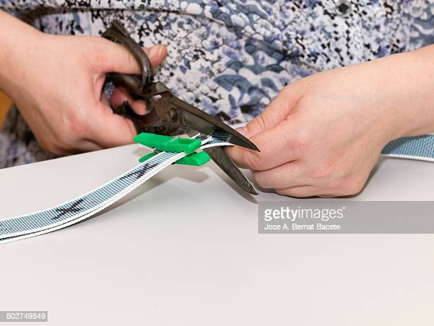 Hands of a woman cutting with scissors