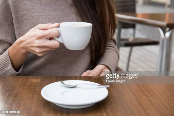 hands of a woman holding a cup of coffee - saucer stock pictures, royalty-free photos & images
