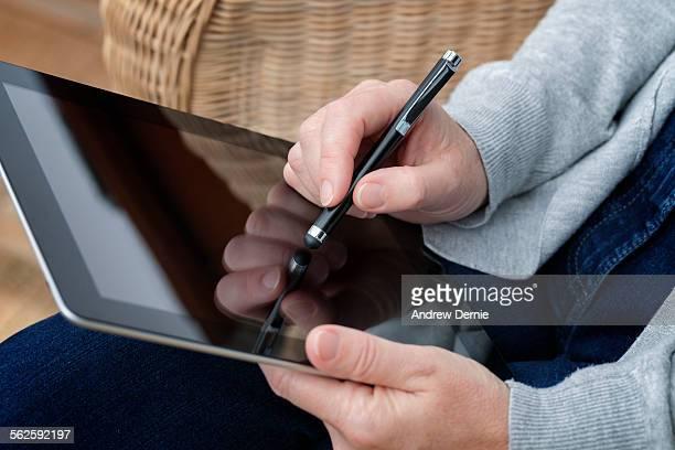 Hands of a women holding a digital tablet
