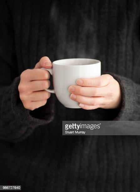 hands of a young woman holding a cup of coffee. - woman cradling mug stock pictures, royalty-free photos & images