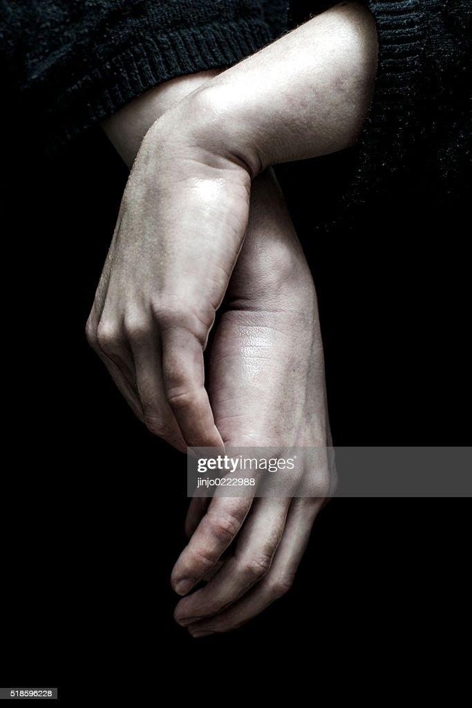 Hand der eine junge Frau isoliert auf dunklem Hintergrund : Stock-Foto