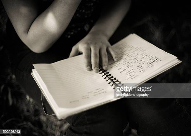 Hands of a youth writes a book outside by a tree