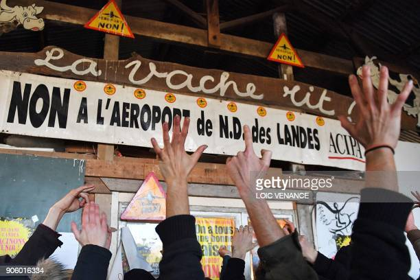 Hands of activists celebrating are pictured at La Vache rit a farm in the 'Zad' of NotreDamedesLandes after French prime minister announced the...