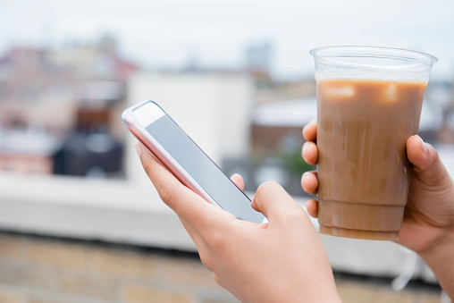 Hands of African American woman drinking coffee and texting on cell phone - gettyimageskorea
