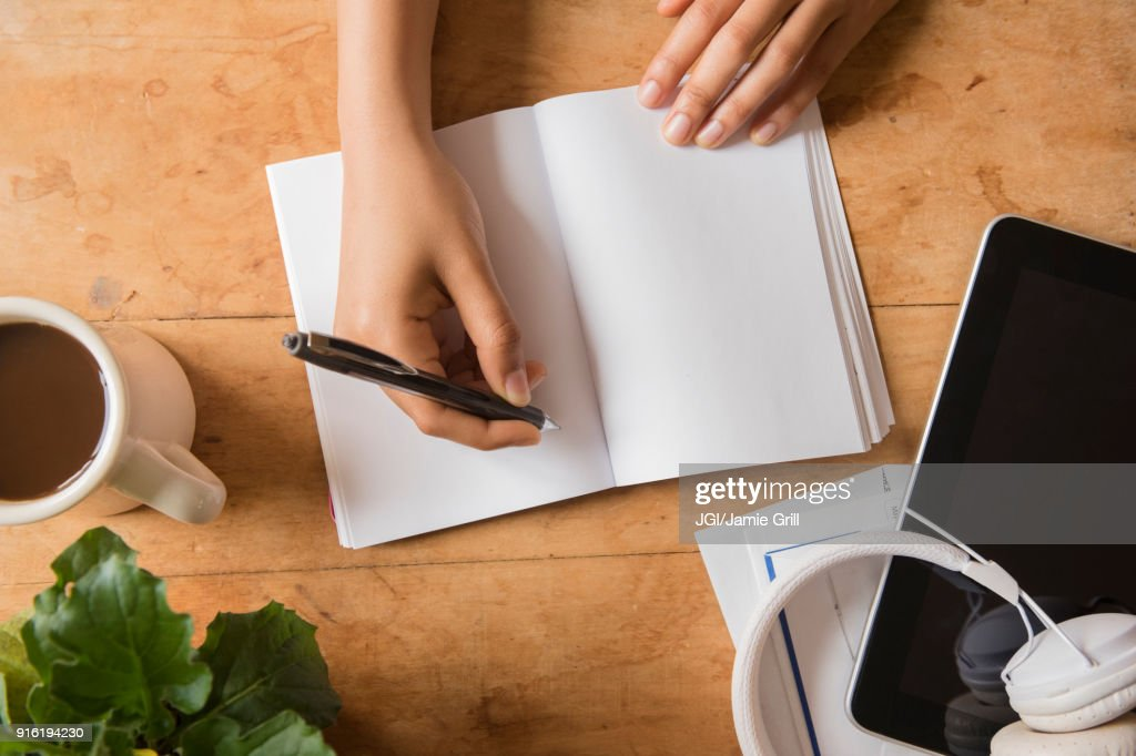 Hands of African American woman writing in journal : Stock Photo