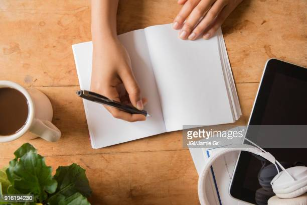 hands of african american woman writing in journal - writing stock pictures, royalty-free photos & images