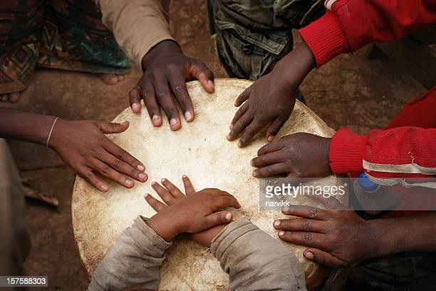 Hands of African Children Playing the Big Drum