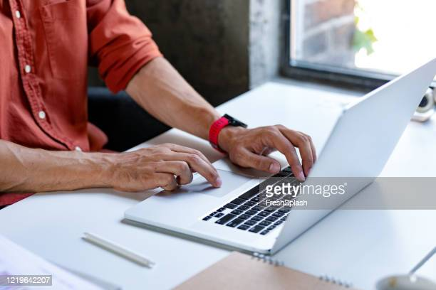 hands of an anonymous businessman in a red shirt typing on a laptop computer - red shirt stock pictures, royalty-free photos & images