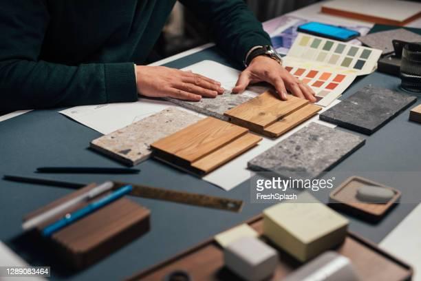 händerna på en anonym manlig inredningsarkitekt jämföra prover av olika material i sitt kontor - wood material bildbanksfoton och bilder