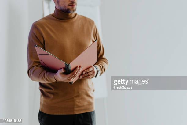 hands of an anonymous male teacher holding his lecture materials (copy space) - polo neck stock pictures, royalty-free photos & images