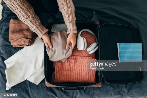 mani di una donna anonima che impacchetta la sua valigia per le vacanze invernali, una vista dall'alto - valigia foto e immagini stock
