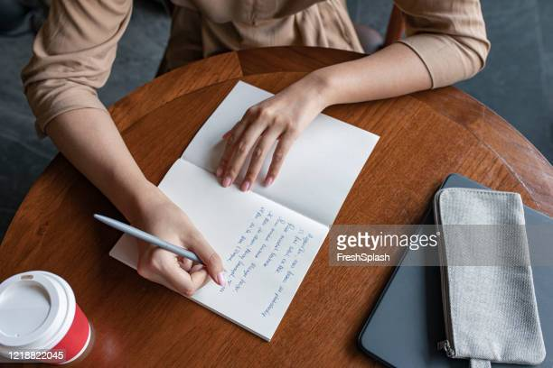 hands of an anonymous woman writing notes in her notebook, a close up - poet stock pictures, royalty-free photos & images