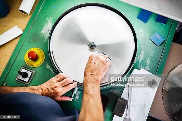 Hands of an industrial worker grinding workpiece