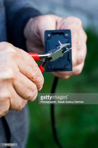 hands of an old man repairing cables, cutting the blue cable with a plier - basak gurbuz derman stockfoto's en -beelden