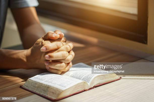 hands of an unrecognizable a man with bible praying - praying hands stock pictures, royalty-free photos & images
