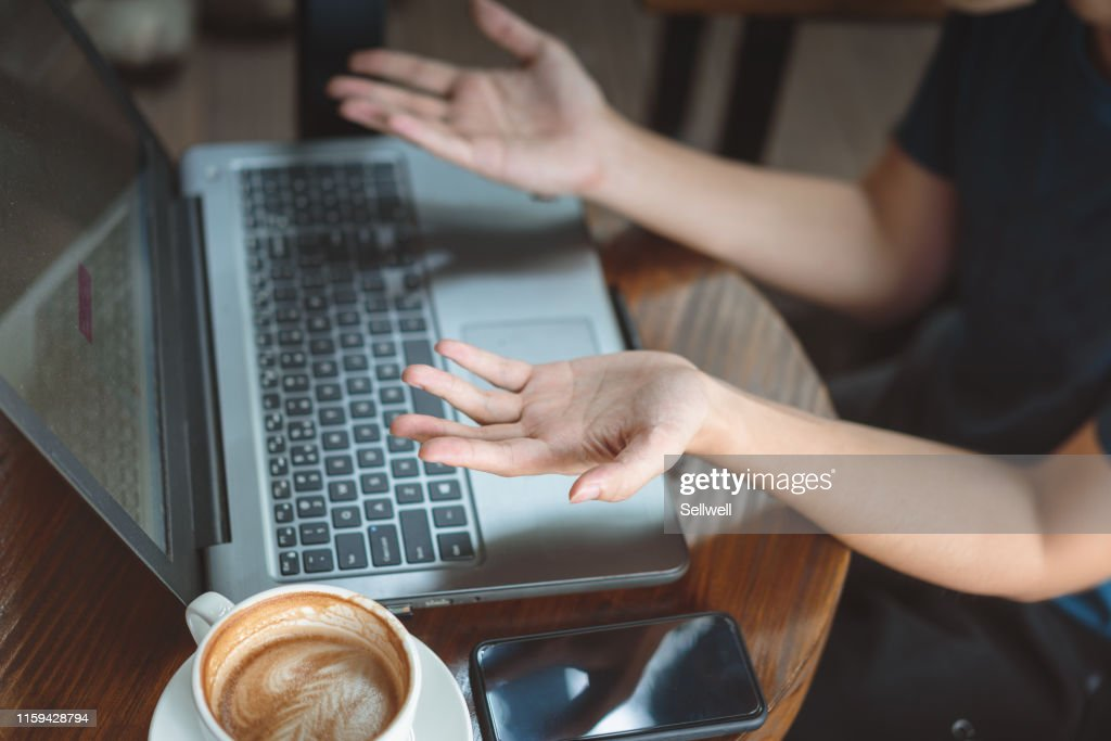 Hands of Asian woman gesturing at laptop in cafe : Stock Photo